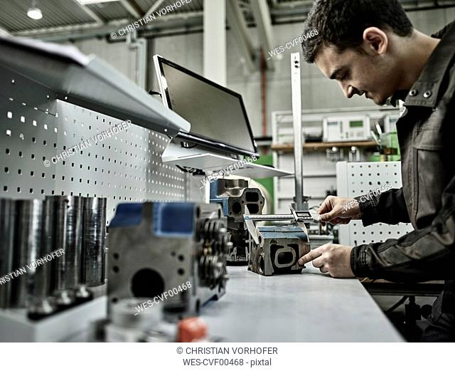 Worker in metalworking factory measuring cylinder head with caliper