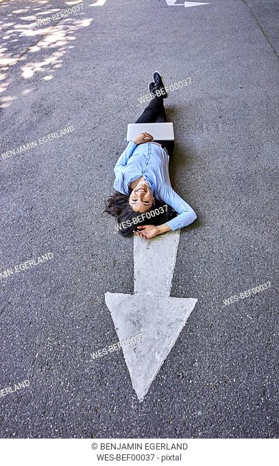Laughing young businesswoman with laptop lying on arrow sign on street