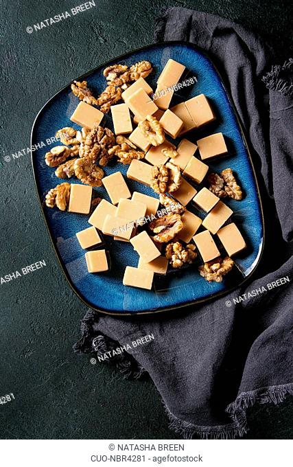 Salted caramel fudge candy served on blue ceramic plate with caramelized walnuts on textile napkin over black texture background. Top view, space