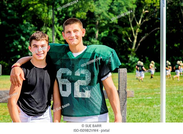 Portrait teenage male American football player with arm around friend at playing field