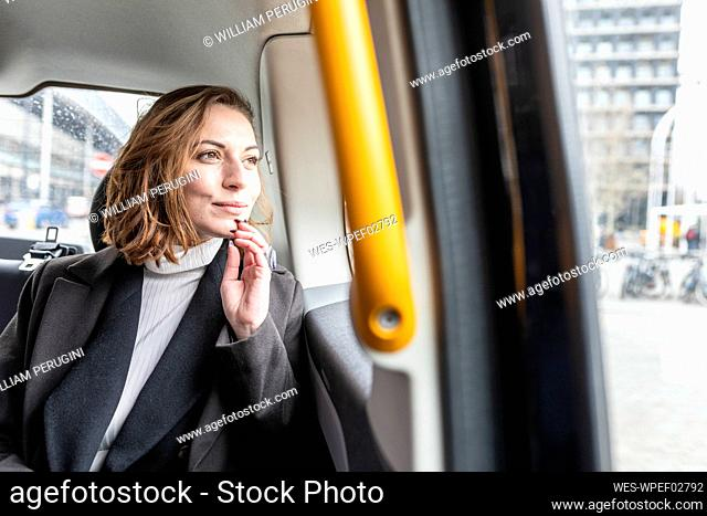 Woman in the rear of a taxi looking out of the window, London, UK