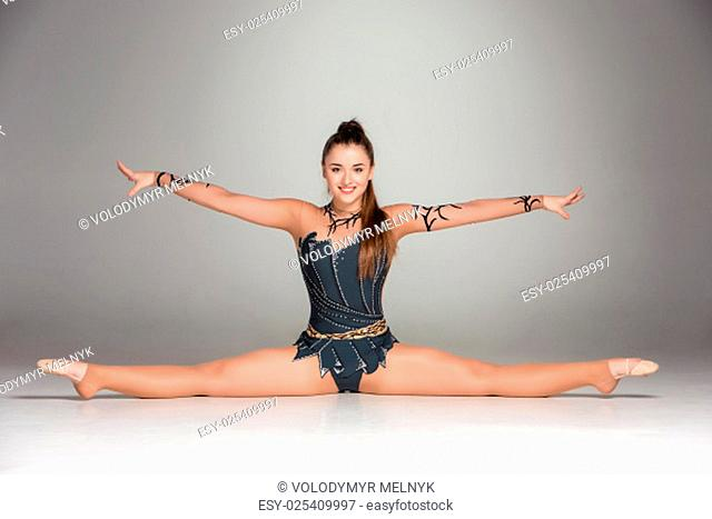 portrait of a gymnast stretching twine on a gray background