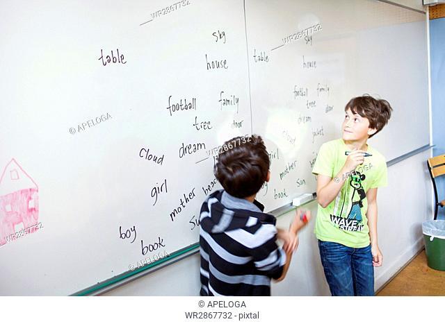 Schoolboys learning spellings on whiteboard in classroom