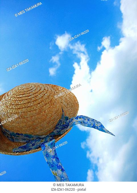 Low angle view of a straw hat in mid-air