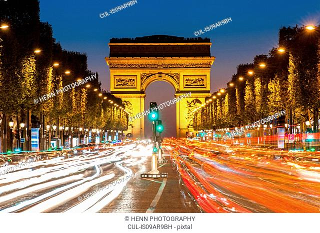 View of the traffic in front of Arc de Triomphe at night, Paris, France