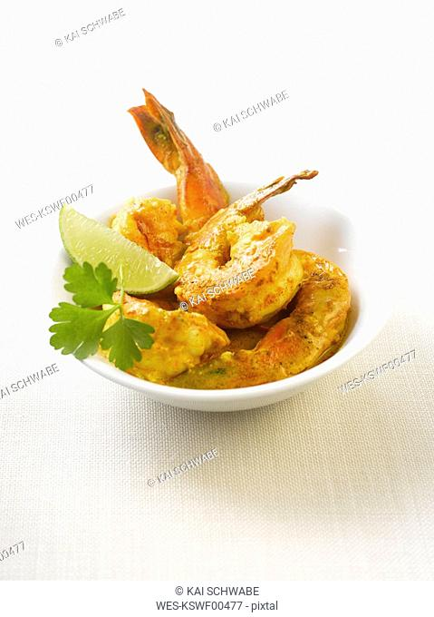 King prawns in curry marinade with lemon slices on plate