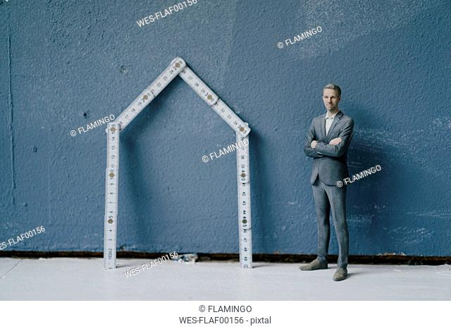 Pastic figurine, businessman and pocket rule as house
