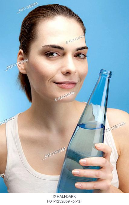 A smiling young woman holding a glass bottle of water
