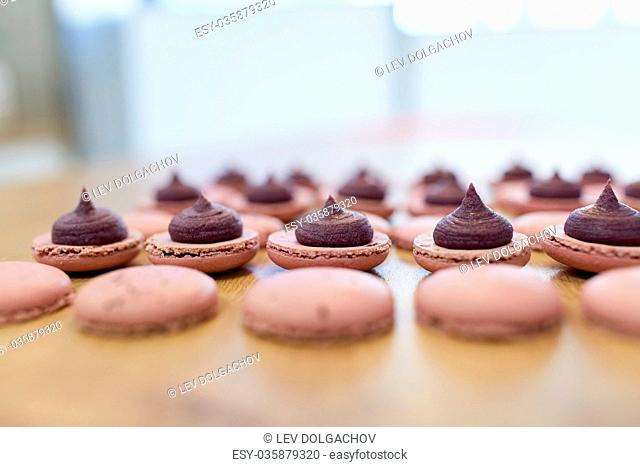 cooking, confectionery and baking concept - macarons with buttercream filling on table at bakery