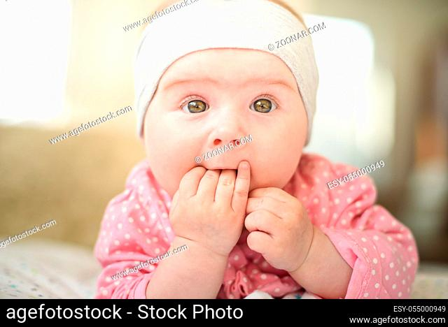 Cute 6 months old Baby girl infant on a bed on her belly with head up looking into camera with her big eyes. Natural bedroom light
