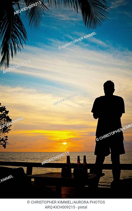 Silhouette Of A Man Watching The Sunset From A Beach On Koh Chang Island, Thailand