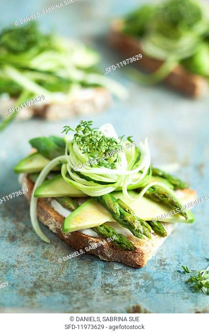 Grilled bread topped with avocado, green asparagus and cress