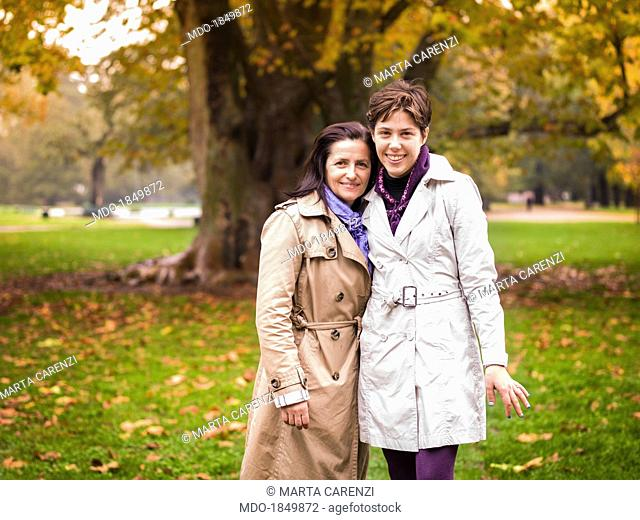 A woman and a girl posing in a garden in autumn. Milan (Italy), October 2013