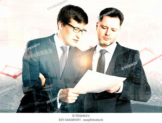 Two handsome businessmen discussing contract together on abstract city background with business chart. Teamwork and economy concept. Double exposure