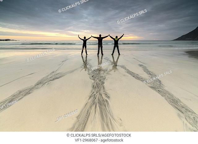 Friends on the beach admire the midnight sun Skagsanden Ramberg Nordland county Lofoten Islands Northern Norway Europe