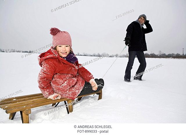 A man pulling a sled daughter on it