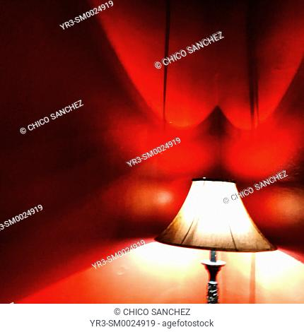 A lamp illuminates a red room in the Hotel California in Todos Santos, Baja California Sur, Mexico. An urban legend tells pop band Eagles composed their album...