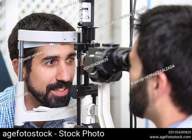 male doctor ophthalmologist is checking the eye vision of handsome young man in modern clinic. Doctor and patient in ophthalmology clinic