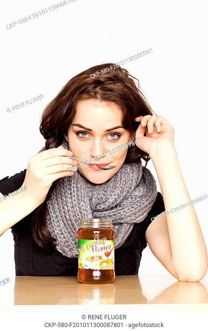 A beautiful young woman, lady, girl, cold, runny nose, headache, cup of tea with honey, spoon, scarf CTK Photo/Rene Fluger