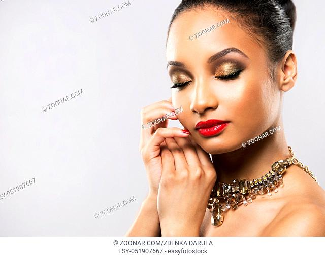 Upscale Indian woman wearing gold jewellery and red lipstick on light background
