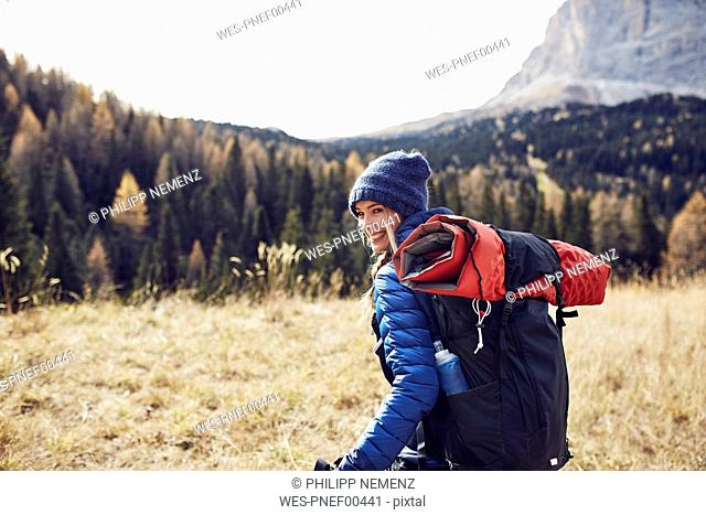 Happy young woman hiking in the mountains