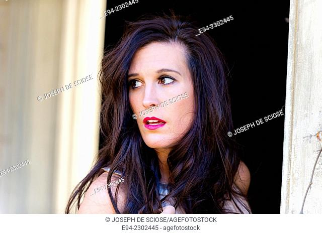 36 year old brunette woman outdoors looking over her shoulder away from the camera