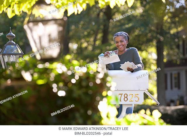 Mixed race woman reading mail at mailbox