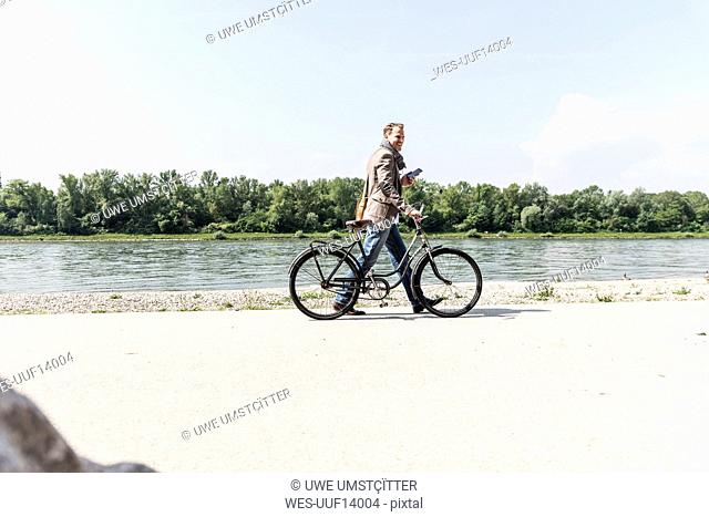 Mature man with bike using smartphone at Rhine riverbank