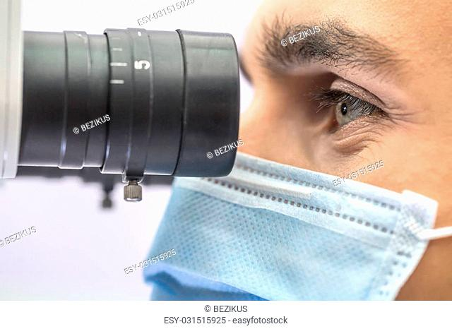Awesome macro photo of a doctor who looks into the dental microscope on the light background. He wears a blue medical mask. Horizontal