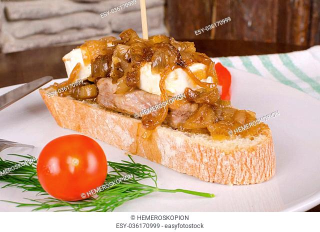 Meat tapa topped with caramelized onion