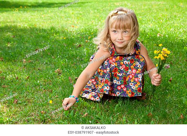 Girl picking flowers on meadow in the park