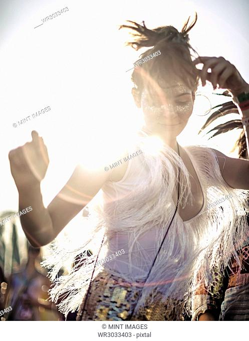 Young woman at a summer music festival in a white vest top with fringes with arms raised, dancing among the crowd