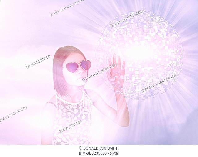Mixed Race girl wearing sunglasses touching hovering pixel sphere