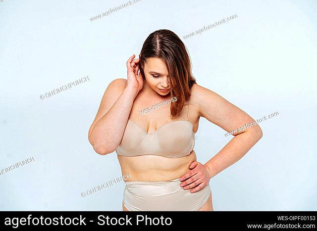 Young woman with hand on hip looking down while standing against white background