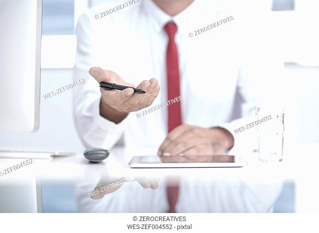Businessman in office holding pen in hand, mid section