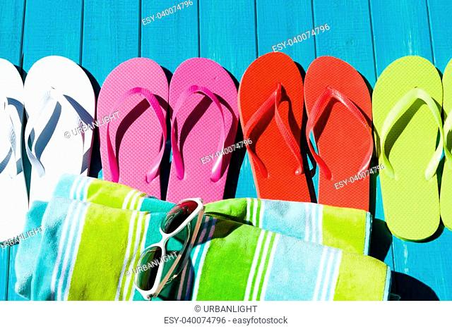 Colorful flip flops by a swimming pool