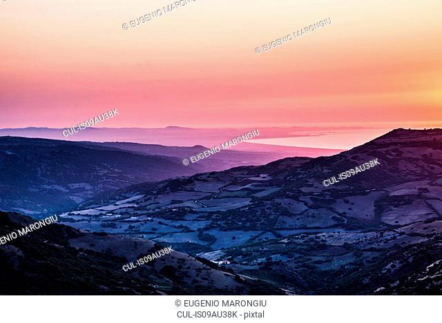 Orange sunset over ocean and rugged mountain farmland, Castelsardo, Sardinia, Italy