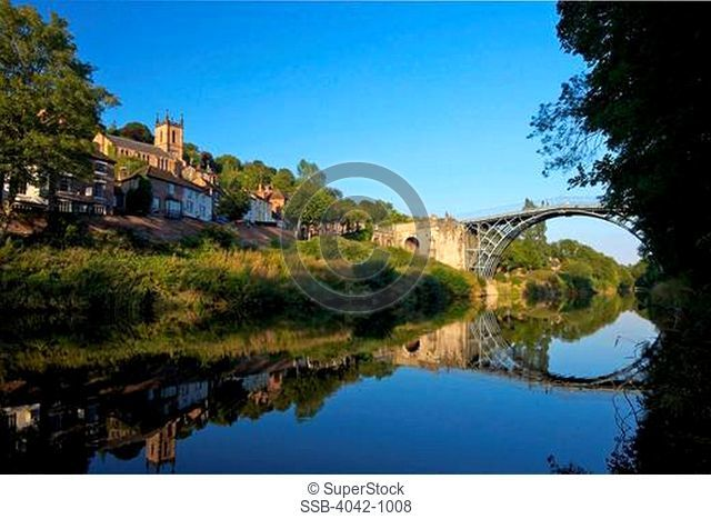 Reflection of an iron bridge and trees in a river, River Severn, Shropshire, England