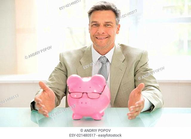 Portrait Of A Happy Businessman With Piggybank Wearing Eyeglasses On Desk