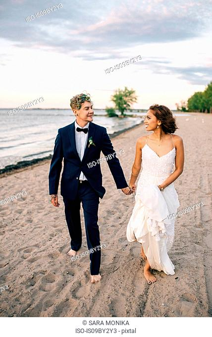 Romantic bride and groom strolling hand in hand on lakeside, Lake Ontario, Toronto, Canada