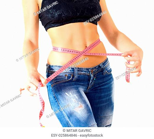 Slim Female with perfect healthy fitness body, measuring her thin waist with a tape measure. Caucasian young woman in jeans, over white background