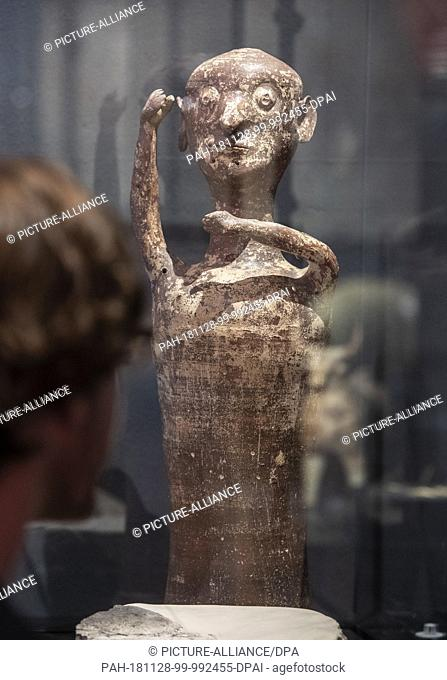 26 November 2018, Baden-Wuerttemberg, Karlsruhe: A person in the Badisches Landesmuseum in Karlsruhe Castle looks at an idol figure from the cult centre of...