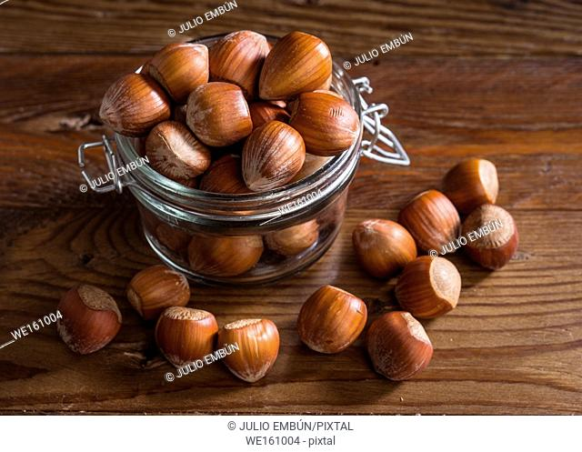 unpeeled hazelnuts in a glass jar, on rustic wood