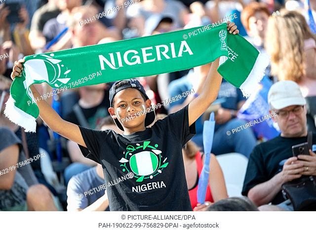 22 June 2019, France (France), Grenoble: Football, women: WM, Germany - Nigeria final round, round of sixteen, Stades des Alpes: A boy is holding up a Nigeria...
