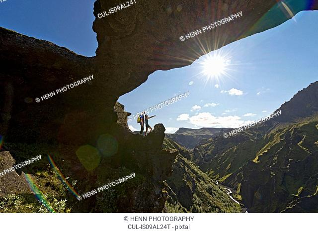 Couple standing in arch on way up to Fimmvordurhals Pass above Thorsmork Valley, Thorsmork, South Iceland, Iceland