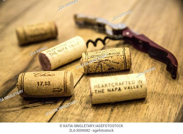Stack of corks and corkscrew on a wooden surface