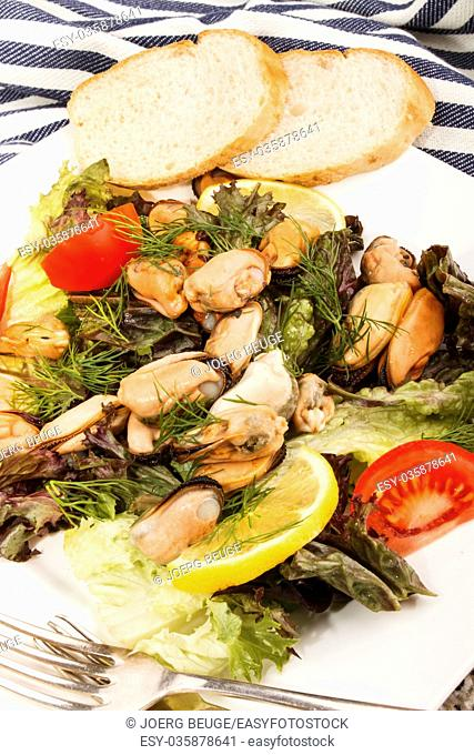 mussel salad with tomato, lemon and bread on a plate