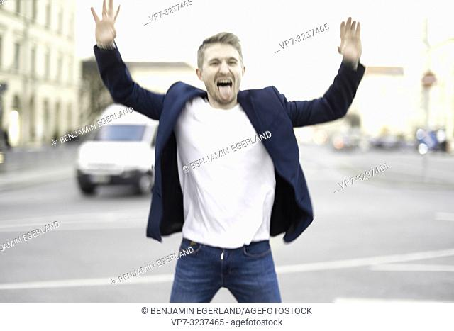 man jumping at street in city, wearing business blazer, stretching out tongue, in Munich, Germany