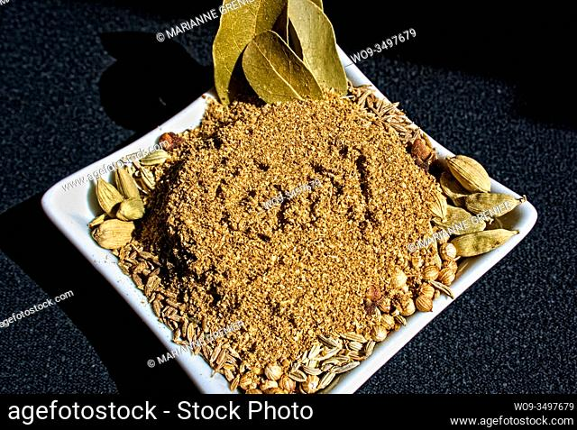 Homemade garam masala spice mix in a white small dish on a dark background close up