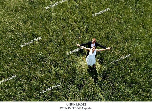 Aerial view of pregnant bride with her husband on a meadow